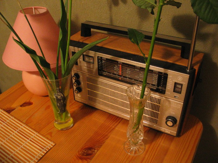 An old radio, two vases and a pink lamp on a table