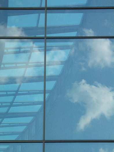 A skylight seen through a window with cloud reflections