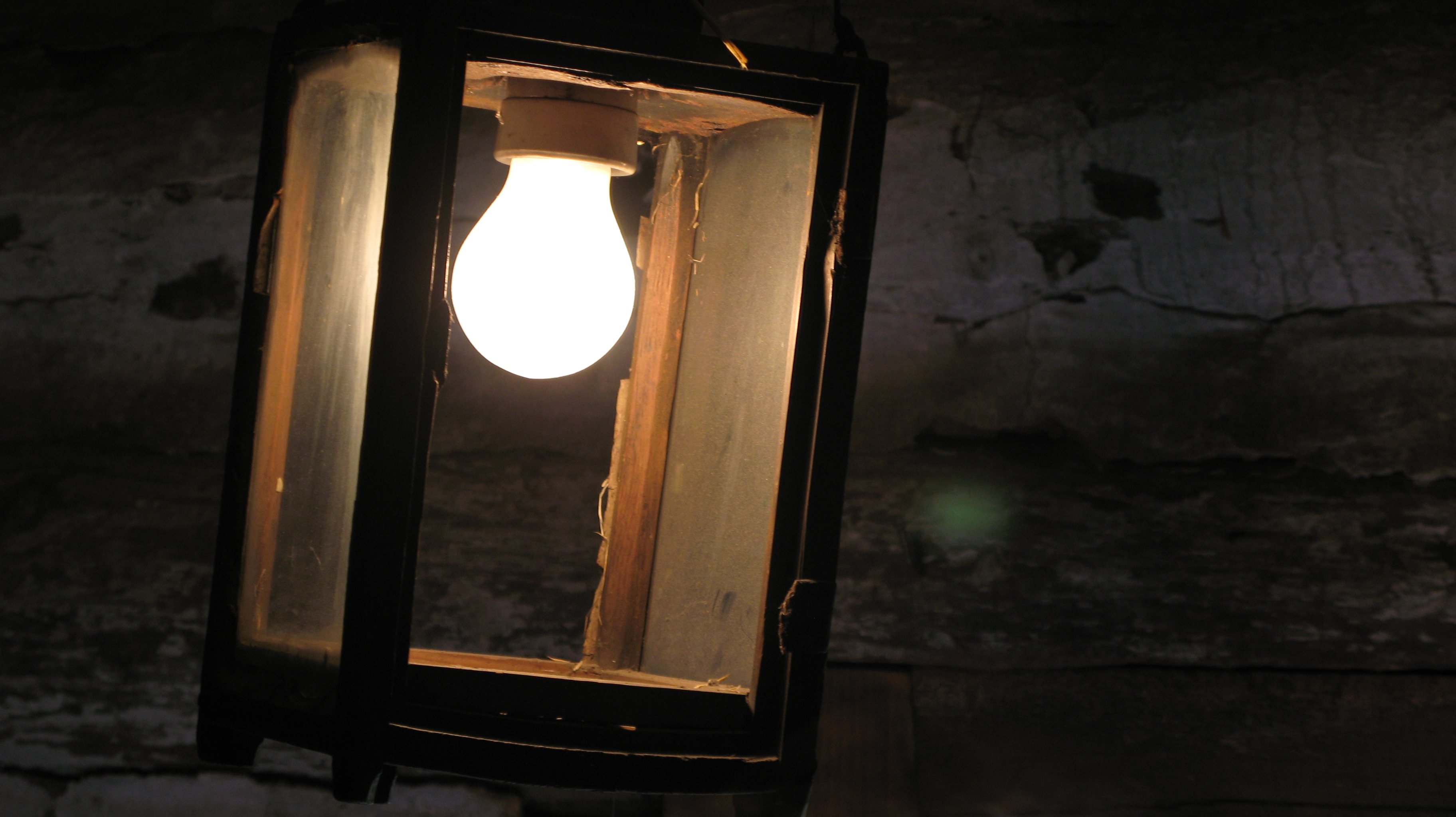 A wooden lantern with a light bulb