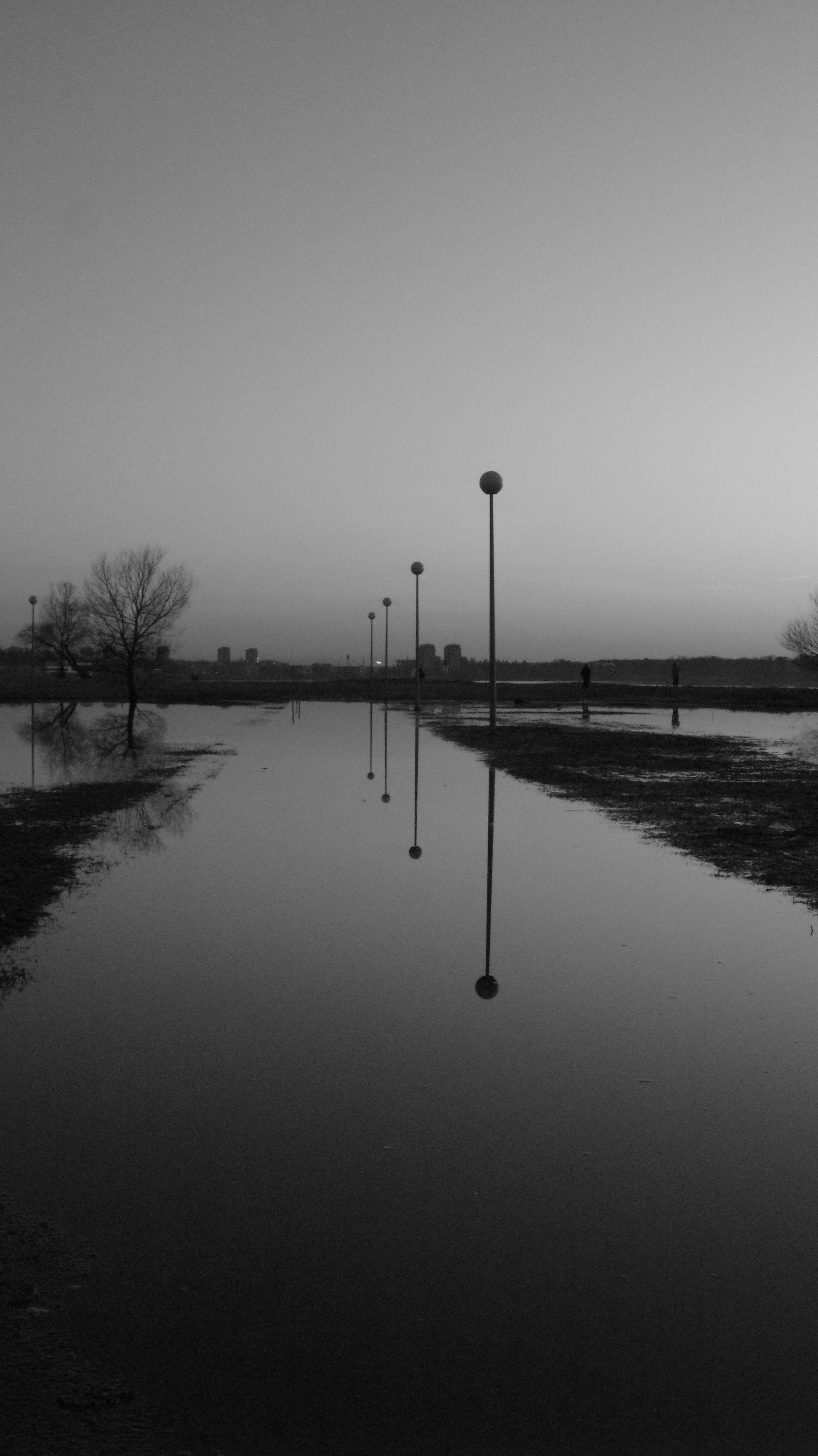 Black and white flooded sidewalk with street lamp along the way