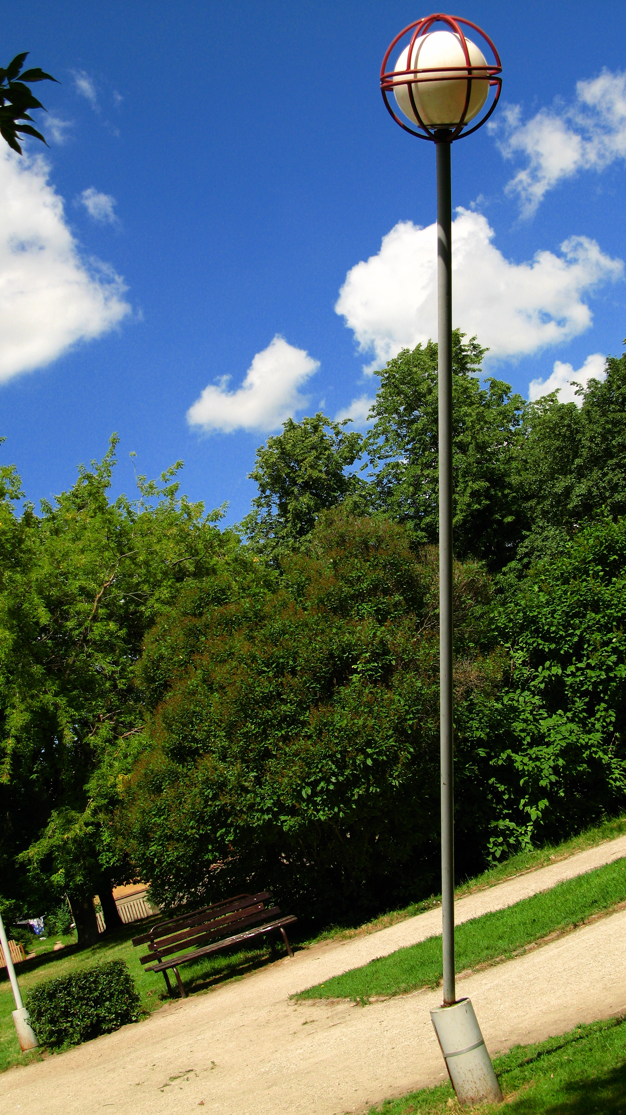 Shot of a skewed street lamp taken so it would appear straight up, a park in the background