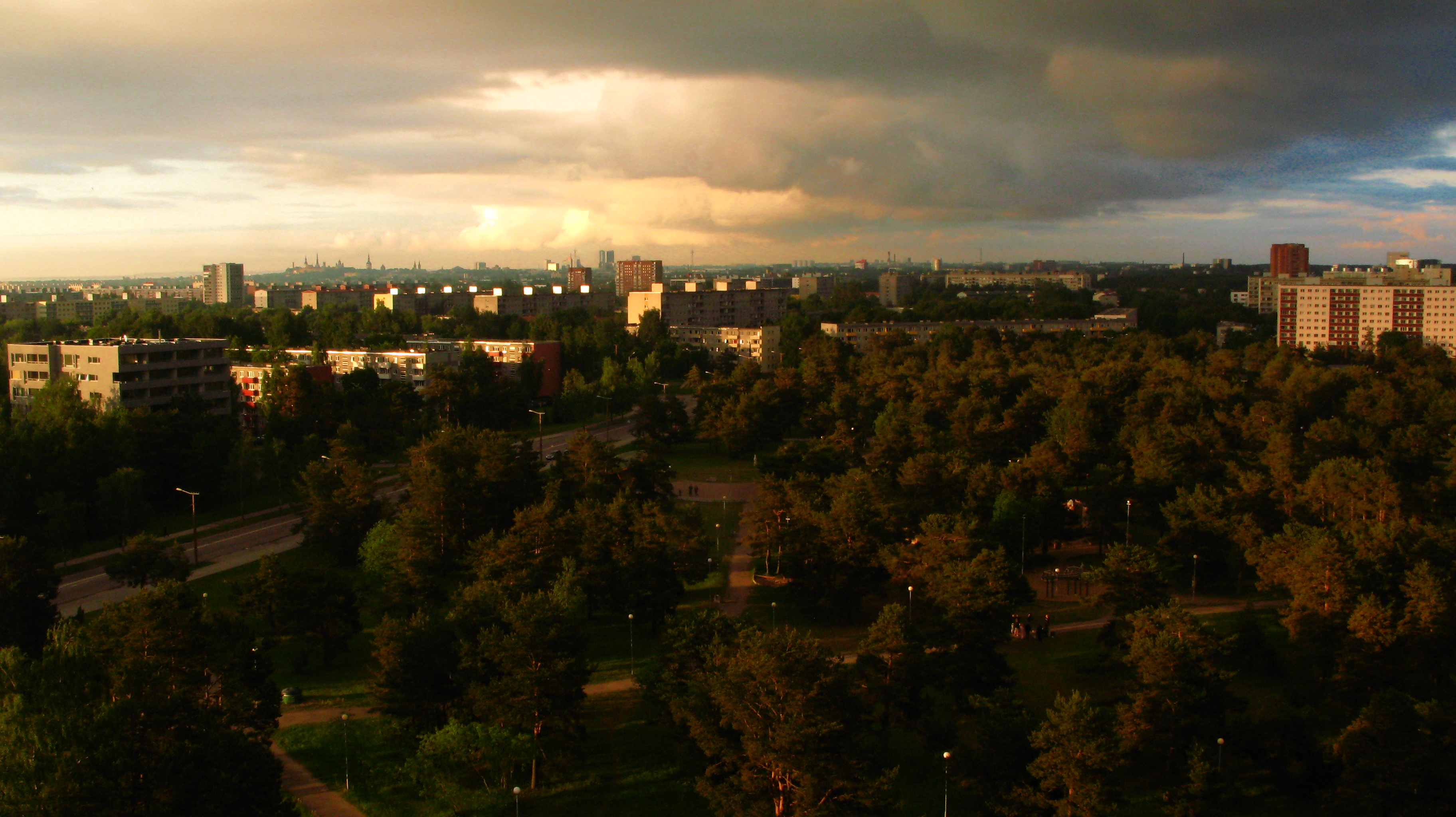 A higher vantage point on a park with the sun shining from a low angle, city center and clouds on the background